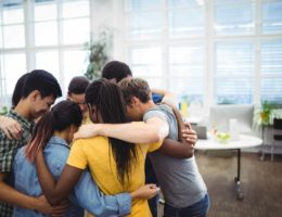 Group of happy business executives forming huddle in office